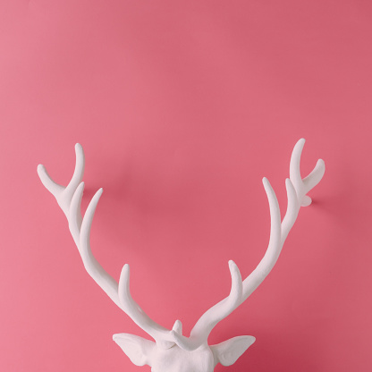 istock White Christmas reindeer head with antlers on pink hipster background. Flat lay. New Year concept. 873267466