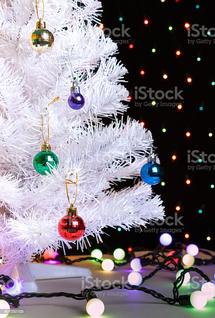 White Christmas Tree Whith Xmas Garland On Blurred Lights Background