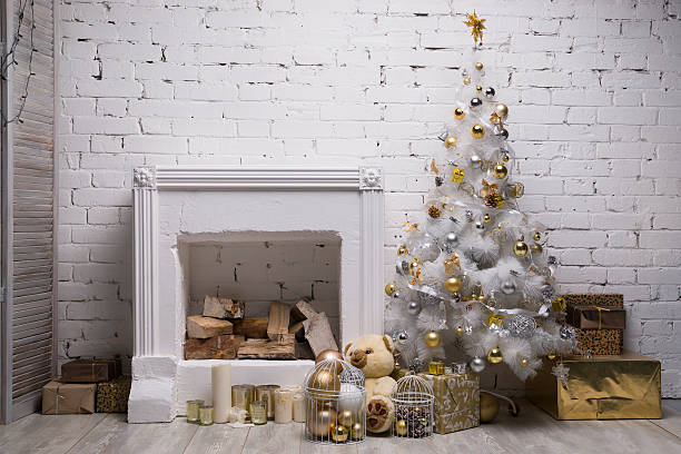 white christmas tree with golden and silver balls, gift boxes - kamin weiß stock-fotos und bilder