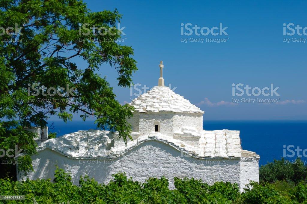Weiße Kirche vor dem blauen Meer, eingerahmt von Büschen und einem Baum, Samos, Griechenland – Foto