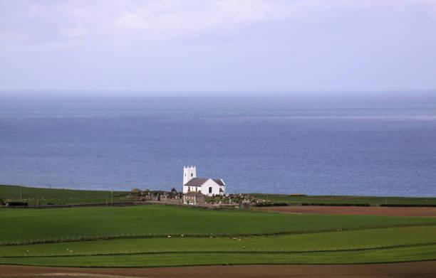 White church on the coast in Ireland next to ocean stock photo