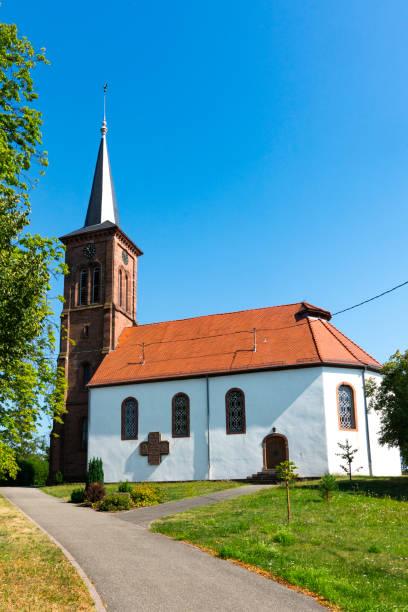 vit kyrka med orange takpannor i hunspach, frankrike - hunspach bildbanksfoton och bilder