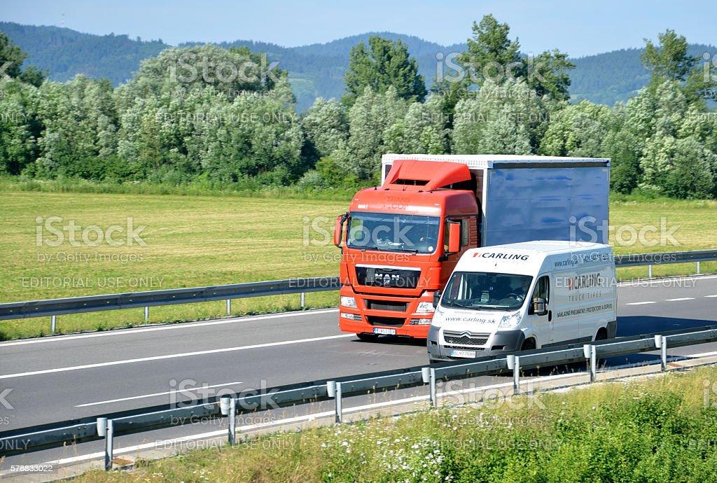 White Citroen van overtakes red MAN truck on slovak D1 highway in...