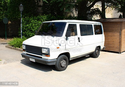 White vintage van is parked on pavement next to the wooden booth