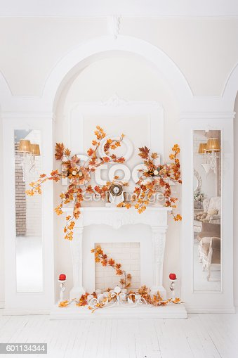 istock White classical fireplace in large hall with autumn decoration 601134344