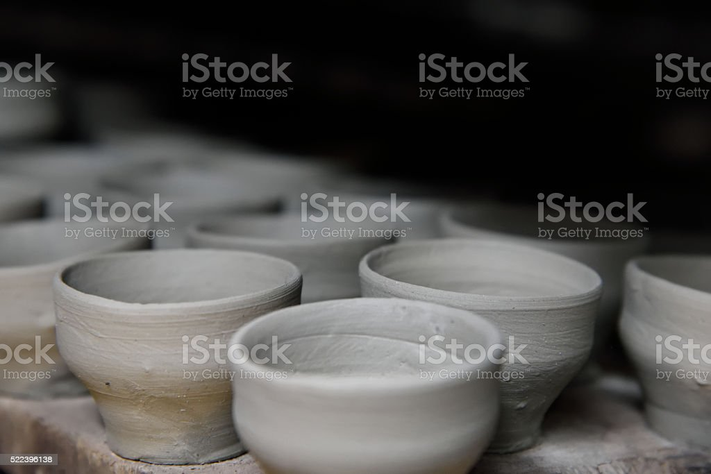 White clay cups drying in a pottery stock photo