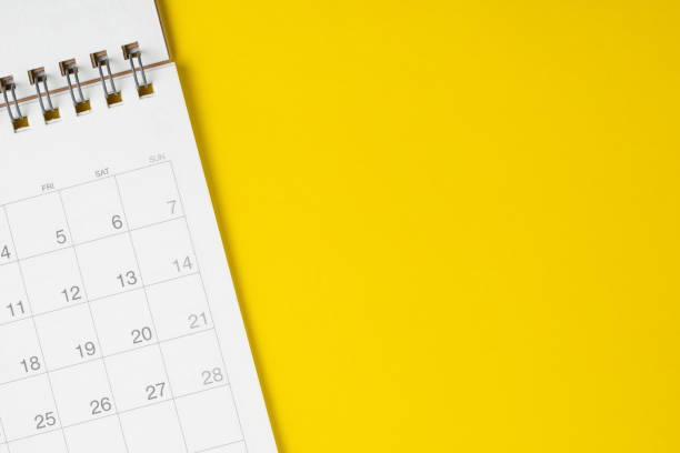 white clean calendar on solid yellow background with copy space, business, travel or project planning concept - deadline stock pictures, royalty-free photos & images