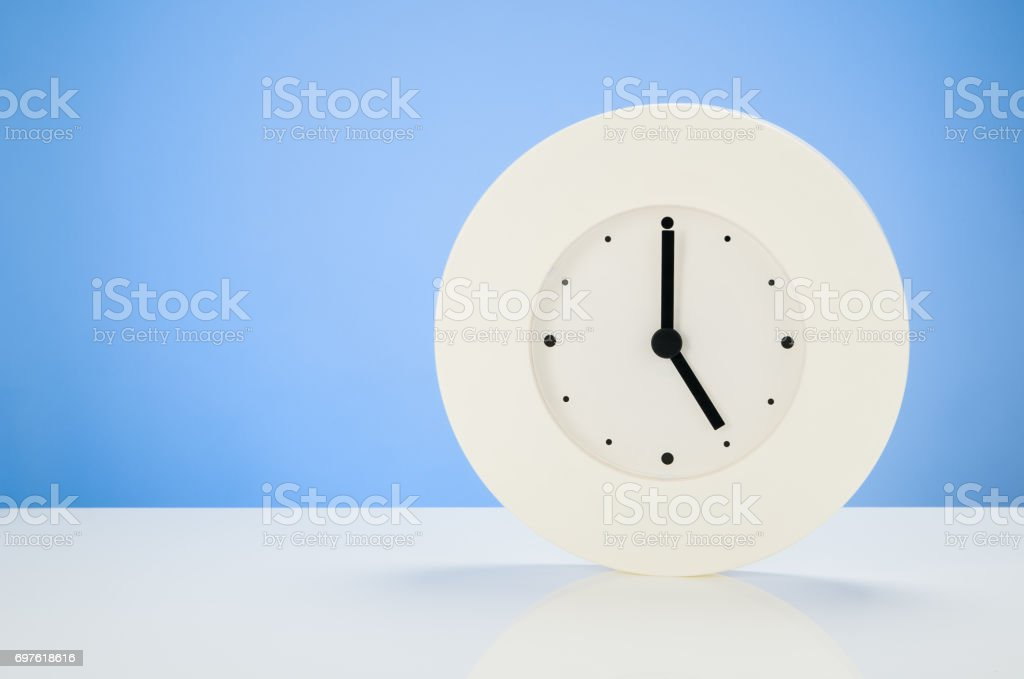 White clock on white table with blue seamless background stock photo