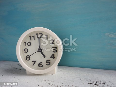 816405814 istock photo White clock pointing to 5 o'clock with white and light blue painted wooden background 1176912666