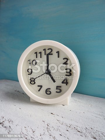 816405814 istock photo White clock pointing to 5 o'clock with white and light blue painted wooden background 1176912676