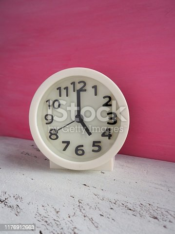 816405814 istock photo White clock pointing to 5 o'clock with white and pink painted wooden background 1176912663