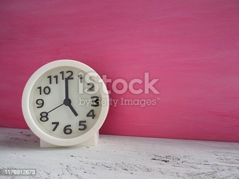 816405814 istock photo White clock pointing to 5 o'clock with white and pink painted wooden background 1176912673