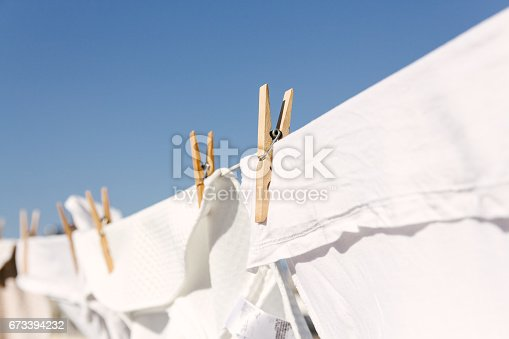 White clothes hung out to dry on a washing line in the bright warm sun. Background is a clear blue sky.