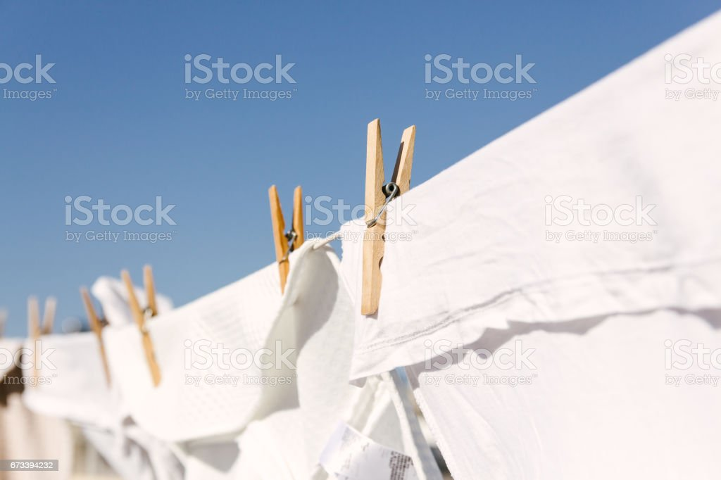 White clothes hung out to dry on a washing line in the bright warm sun. Background is a clear blue sky. stock photo