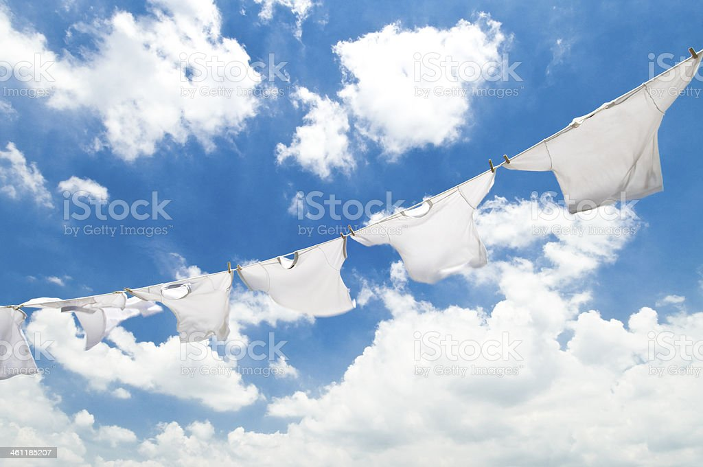 White clothes on a clothesline against a cloudy sky stock photo