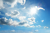 istock white clouds and sun in blue sky 1200224188