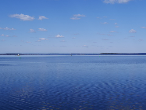 White clouds in the blue sky reflected on the surface of calm water. the ripples on the water.