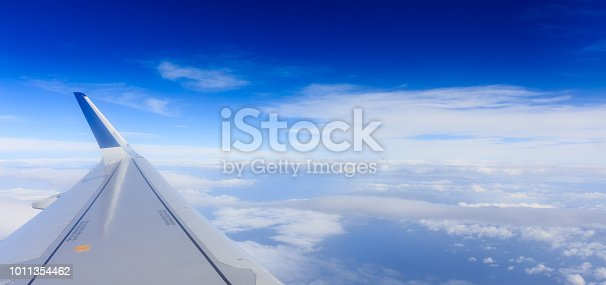 istock White clouds on a blue sky from a plane window background. Space for text. 1011354462