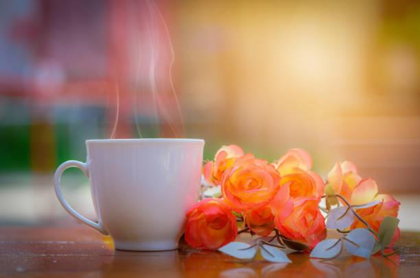 weiße kaffeetasse und rosenblumen auf holztisch mit verschwommenem hintergrund. - rosen tee stock-fotos und bilder
