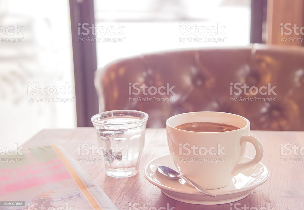 White coffee cup ,blurred newspaper and glass water. royalty-free stock photo