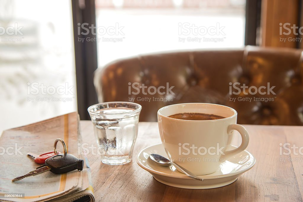 White coffee cup , blurred newspaper, car key  and glass water. Lizenzfreies stock-foto