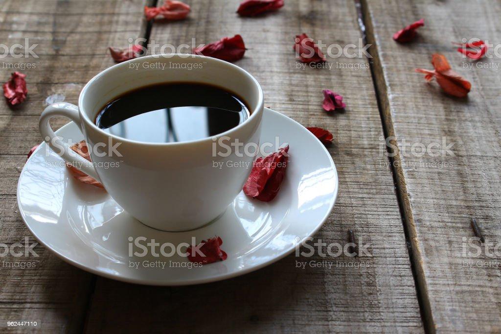 Xícara de café branca decorar com vermelha rosa seca na placa de madeira, conceito vintage. - foto de acervo