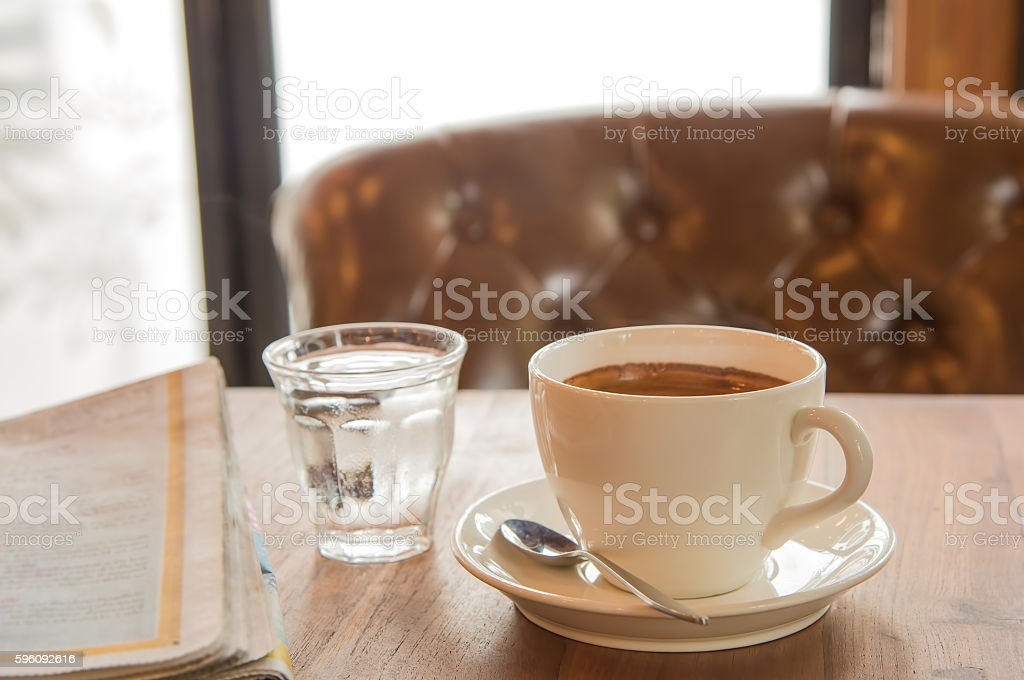 White coffee cup ,Newspaper and glass water on wooden table. Lizenzfreies stock-foto