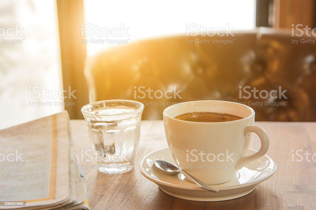 White coffee cup ,Newspaper and glass water on wooden table. royalty-free stock photo