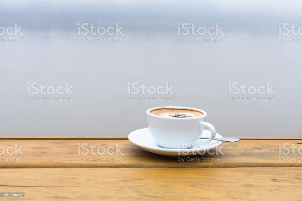 White coffee cup on wood table beside the river view stock photo