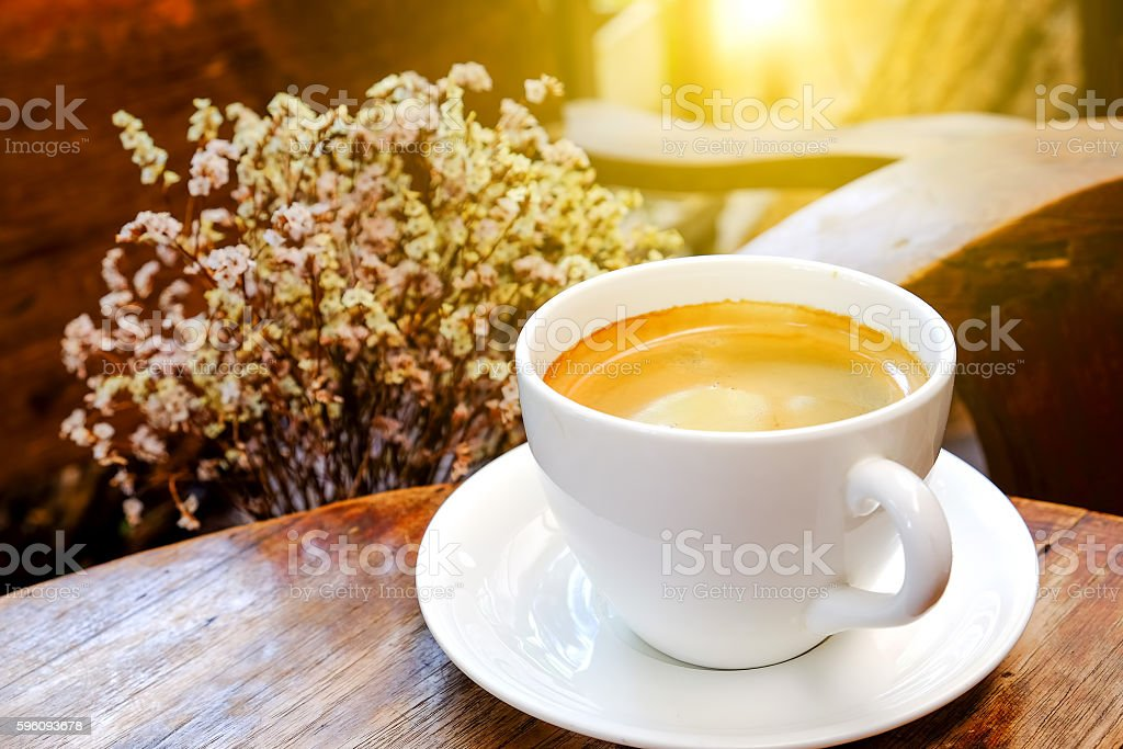 White coffee cup with dry flower on wooden table.. Lizenzfreies stock-foto