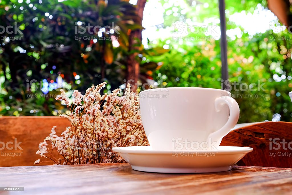 White coffee cup with dry flower on wooden table.Focus coffee. royalty-free stock photo