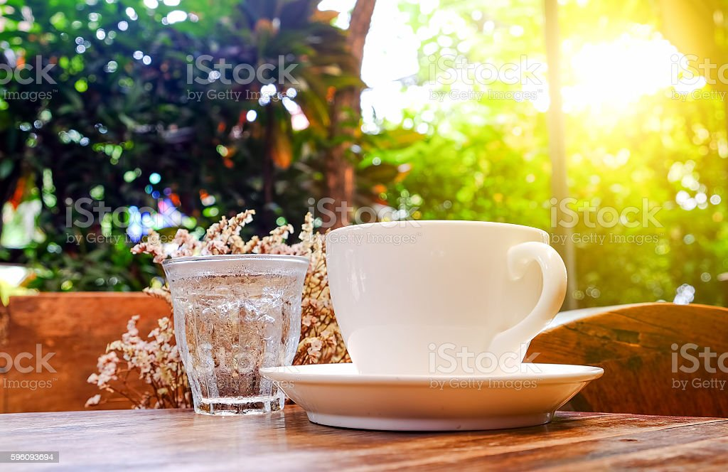 White coffee cup with glass water on wooden table. royalty-free stock photo