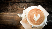 Close up white coffee cup with heart shaped latte art foam and tiny white flower on wood table near window with light shade on table top at cafe in top view.