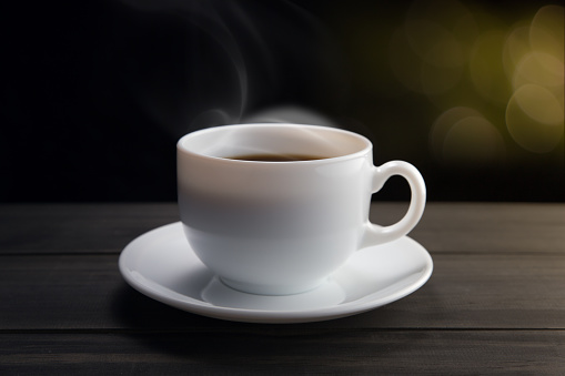 White coffee cup with smoke on black background. Dark background