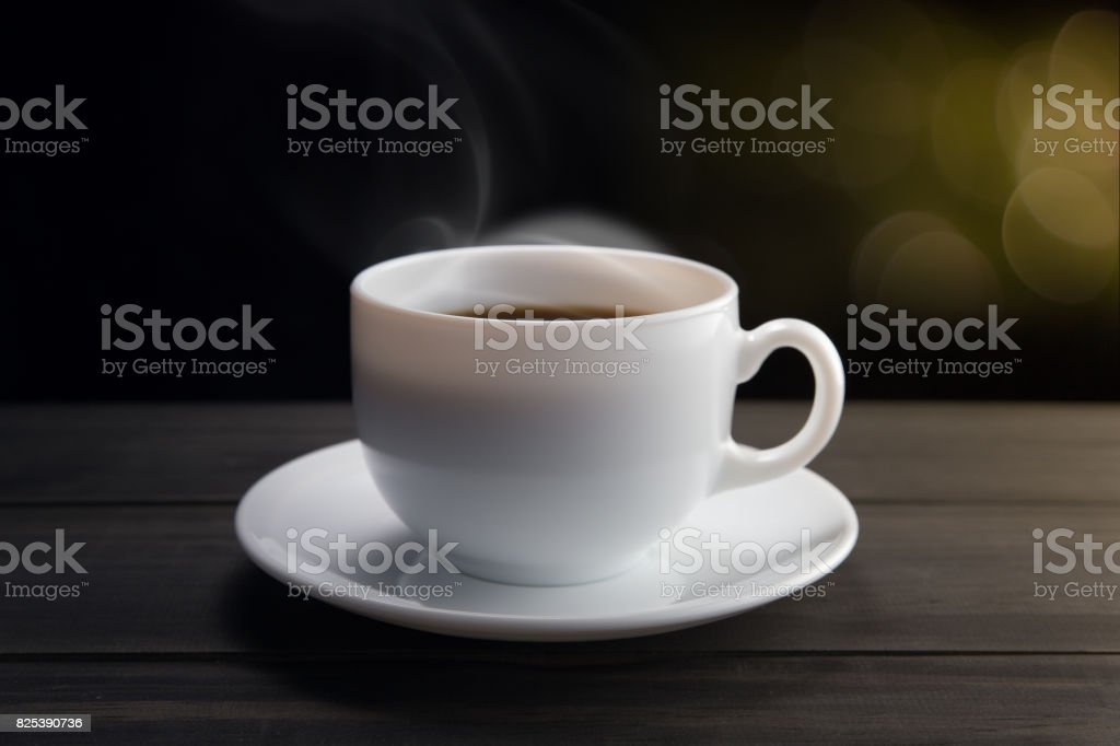 White coffee cup with smoke on black background. Dark background stock photo