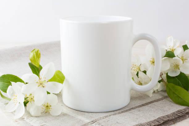 White coffee mug mockup with apple blossom stock photo