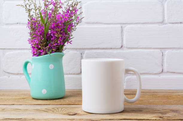 White coffee mug mockup with maroon purple flowers in mint pitcher stock photo