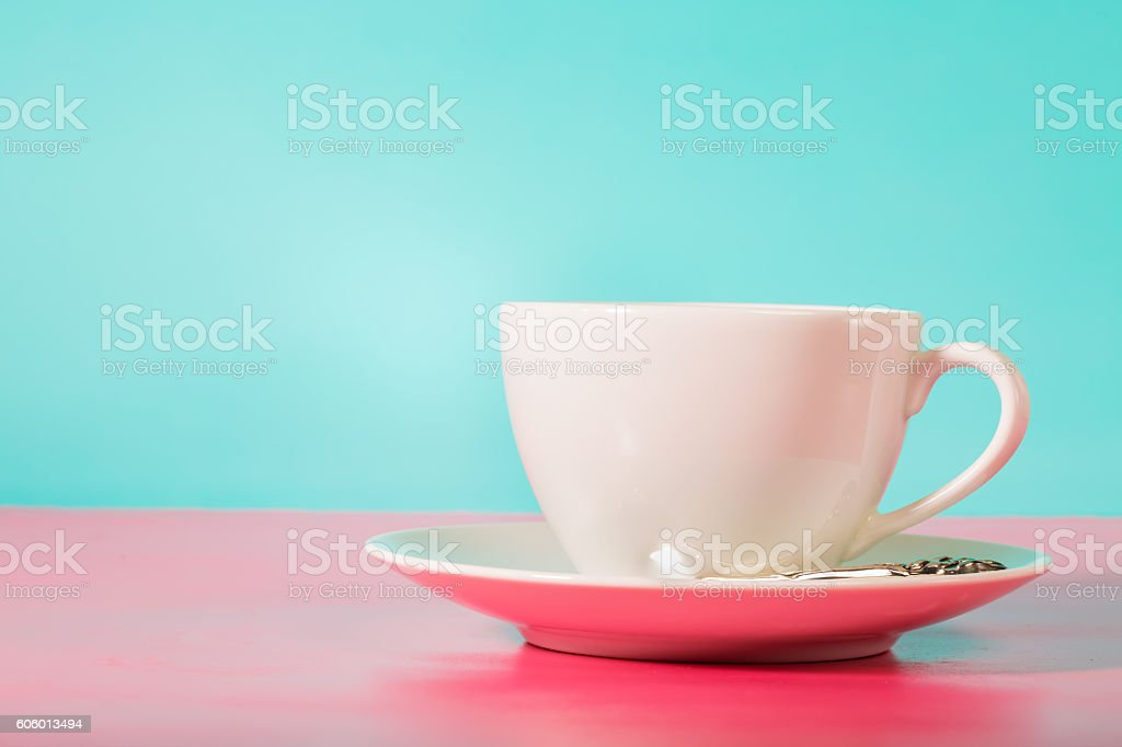 White coffee mug on bright pink and blue background stock photo