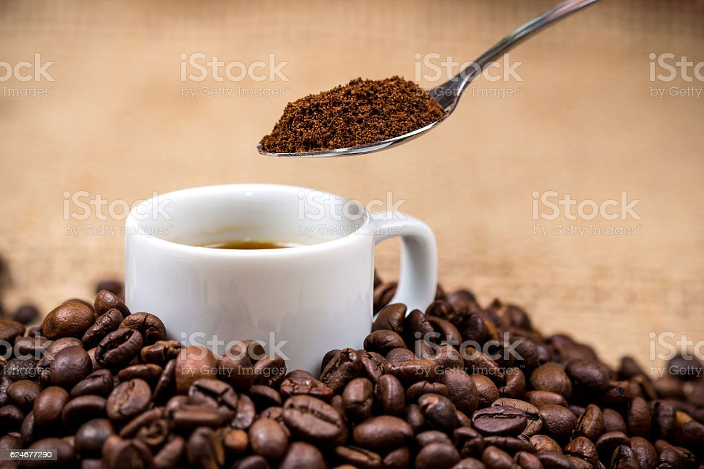 White coffeecup on coffeebeans with spoon above stock photo