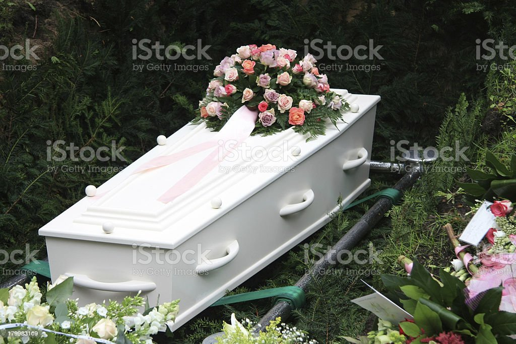 A white coffin with pink flowers stock photo