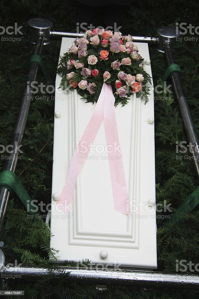 White coffin with pink sympathy flowers royalty-free stock photo