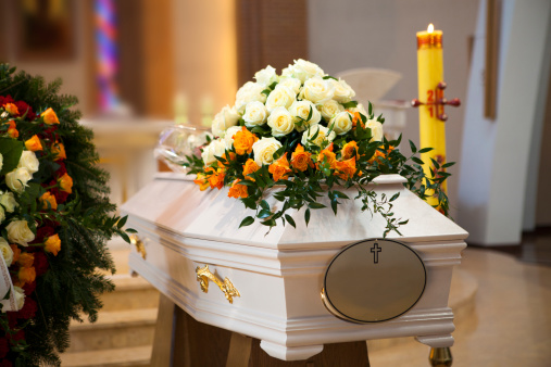 White Coffin, wreath, candle in the Catholic Church