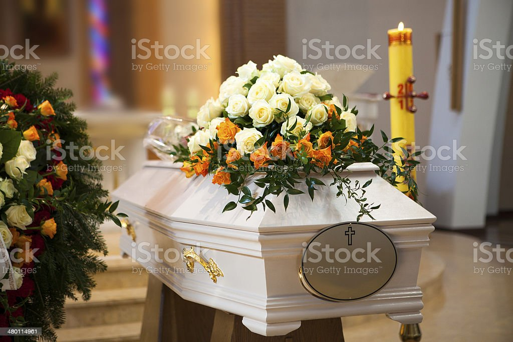 White Coffin, wreath, candle in the Catholic Church stock photo