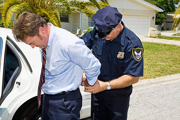 White Collar Criminal Businessman being handcuffed and placed under arrest in front of his home. uniform cap stock pictures, royalty-free photos & images
