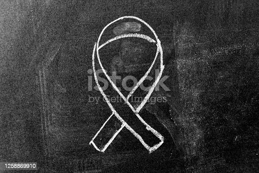 istock White color chalk drawing as black ribbon shape on black board background (Concept for symbol of remembrance or mourning) 1258869910