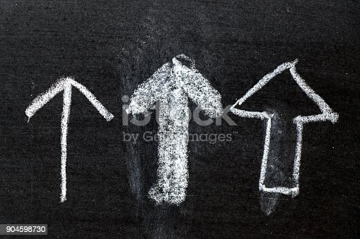 istock White color chalk hand drawing as arrow shape on black board background 904598730