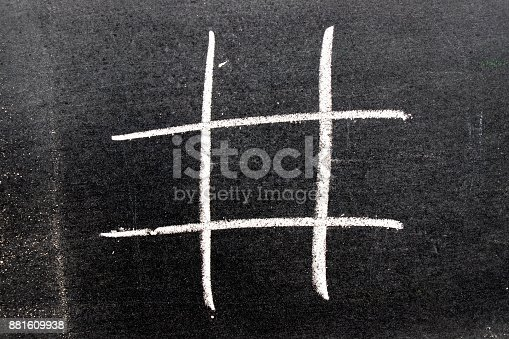 istock White color chalk hand drawing as hashtag shape on blackboard backgroung 881609938