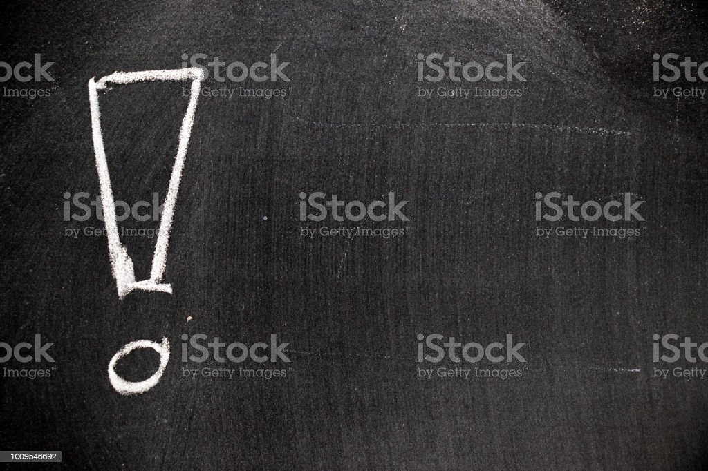 White color chalk hand drawing in exclamation mark with blank space shape on blackboard background stock photo