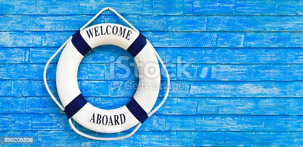 istock White color Life buoyancy with welcome aboard on it hanging on blue wall. 695208836