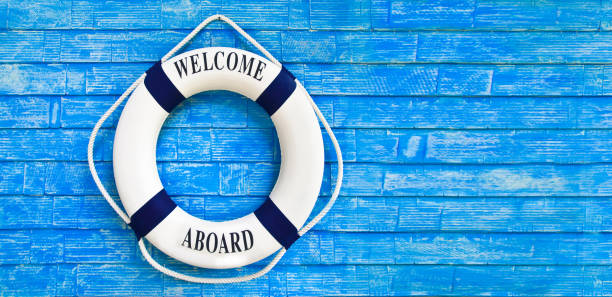 White color Life buoyancy with welcome aboard on it hanging on blue wall. White color Life buoyancy with welcome aboard on it hanging on blue wall. had space on right side for your text. aboard stock pictures, royalty-free photos & images